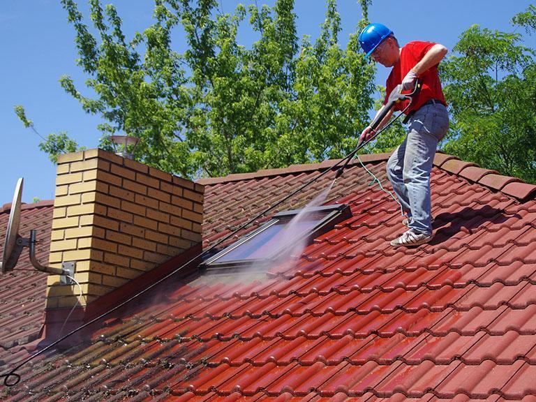 Pracownik myje dach